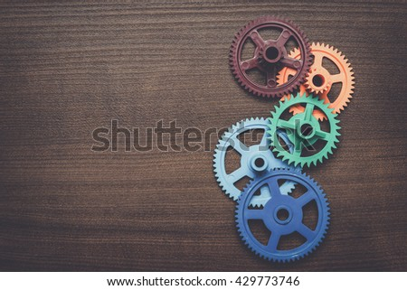 colorful gears on the brown wooden background - stock photo