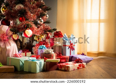 Colorful gift boxes with ribbon and christmas tree with baubles next to a window.