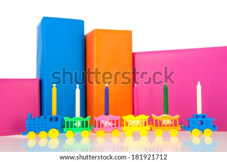 Colorful gifts with little train and birthday candles isolated over white background - stock photo