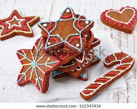Colorful gingerbread cookies on white wooden background
