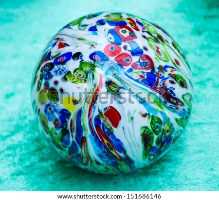 Colorful glass marble ball isolated on turquoise velvet background.  - stock photo