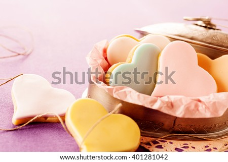 Colorful glazed heart shaped cookies with fondant filling served in an old oval tin on a lilac background with copy space for your Valentines, anniversary or wedding greeting - stock photo