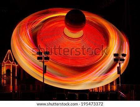 Colorful glowing amusement ride taken with a long exposure