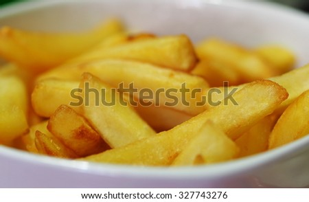 colorful gold short and long pieces of potato french fries, snacks in white porcelain ceramic bowl ready to serve as well known high calories fast food dish. - stock photo