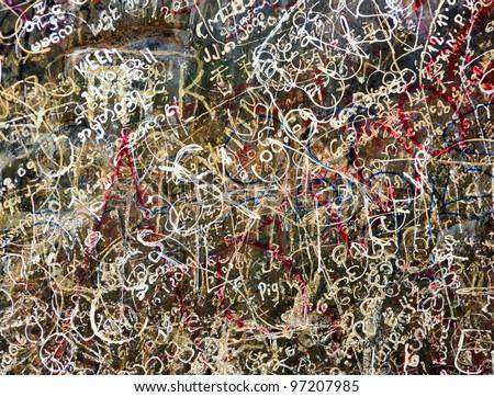 colorful graffiti scratchwork on a stone wall - stock photo