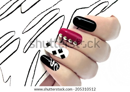 Colorful graphic manicure on an oval shaped nails are covered with black,white,red lacquer. - stock photo