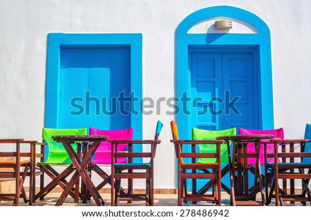 Colorful Greek restaurant table and chairs in front of iconic blue wooden doors and white walls in Greece - stock photo
