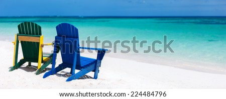 Colorful green and blue lounge chairs at tropical beach in Caribbean with beautiful turquoise ocean water, white sand and blue sky - stock photo