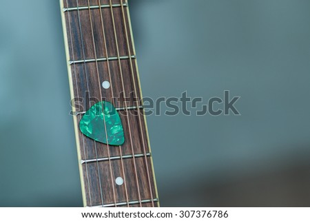 colorful green guitar pick on finger board, as abstract background - stock photo