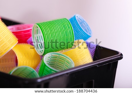 Colorful hair rollers curlers in black basket in hairdressing beauty salon. By hairdresser hairstylist. Hairstyle.