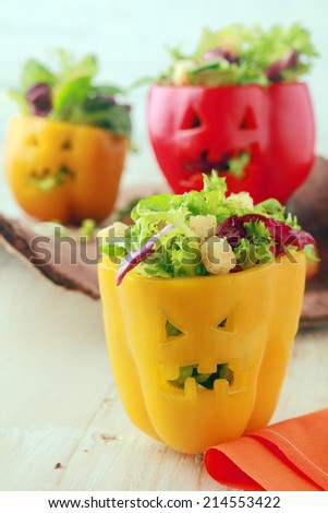 Colorful Halloween food background with creative stuffed red and yellow sweet bell peppers with faces cut into the skin like Halloween pumpkin lanterns filled with fresh green salad and cheese - stock photo