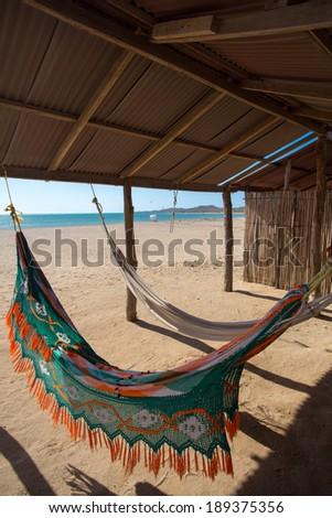 Colorful hammocks on a beautiful deserted bach in Cabo de La Vela in La Guajira, Colombia - stock photo