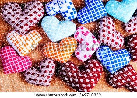 colorful hand made hearts on wood with snow effect - stock photo