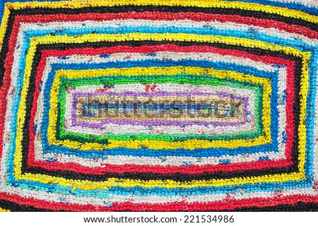 Colorful hand made knitted rug. Reuse of supermarket plastic bag, package. Folk nation creativity. Rustic style. Rough texture  and bright design - stock photo