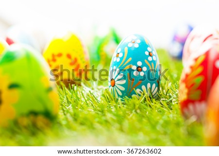 Colorful hand painted Easter eggs in grass. Spring theme, white copy-space. Traditional decoration, unique handmade design.  - stock photo