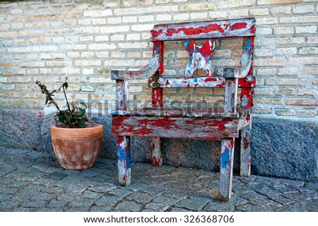 Colorful hand painted old wooden chair in a city street by a brick wall                                - stock photo