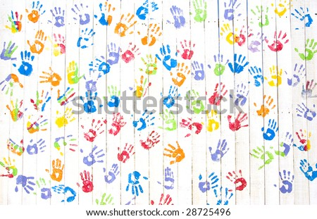 Colorful handprints on a while wooden wall - stock photo