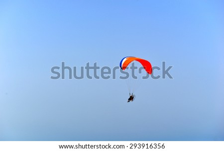 colorful hang glider in sky over blue sea - stock photo