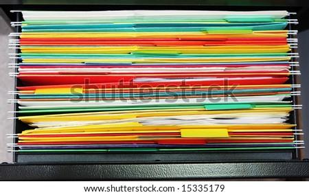 Colorful hanging file folder in black metal drawer - stock photo