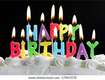 Colorful happy birthday candles burning on a cake - stock photo
