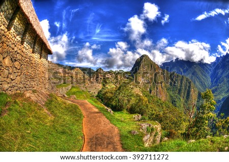 Colorful HDR image of a trail in Machu Picchu, the lost Incan City of Machu Picchu near Cusco, on a clear blue sky - stock photo