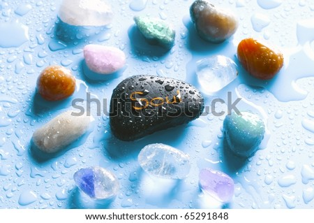 Colorful healing stones gemstones and a stone with the word soul over bright blue background with drops of water - stock photo
