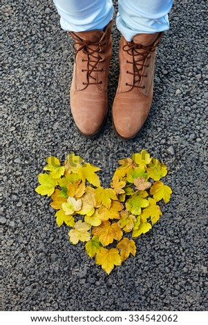 Colorful heart made of autumn leaves, woman shoes on asphalt, concept - stock photo