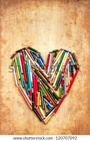 Colorful heart  on vintage old wooden surface/Old colorful pencils as heart/Valentines day background/original card with pencils - stock photo