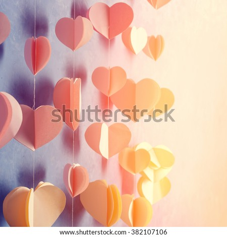 Colorful hearts paper garland hanging on the wall. Romantic Valentine's day background. Instagram style toned photo with copy space for your text - stock photo