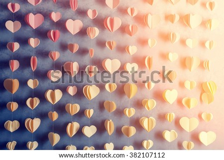 Colorful hearts paper garland hanging on the wall. Romantic Valentine's day background. Instagram style toned photo  - stock photo