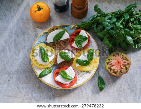 Colorful heirloom tomatoes salad with mozzarella on a stone background/counter top  - stock photo
