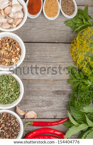 Colorful herbs and spices selection. Aromatic ingredients on wood table with copyspace - stock photo