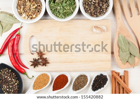 Colorful herbs and spices selection. Aromatic ingredients on wood table with cutting board for copyspace - stock photo