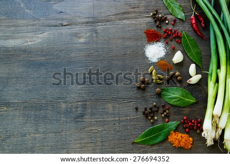 Colorful herbs and spices selection on dark wooden table. Background with space for text. - stock photo