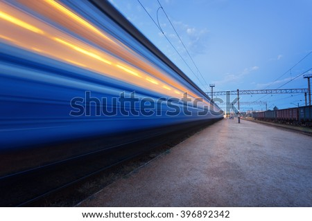 Colorful high speed passenger train on tracks in motion at rural railway station at sunset - stock photo
