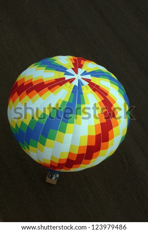 colorful hot air balloon against ground - stock photo
