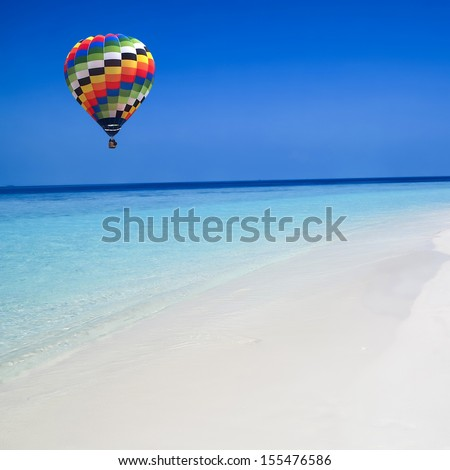 Colorful hot air balloon fly over the blue sea - stock photo