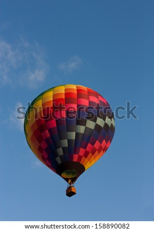 Colorful hot air balloon in a blue sky - stock photo