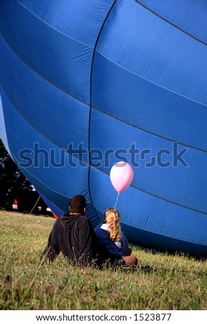 Colorful Hot Air Balloon on Ground with Father and Daughter sitting and Watching - stock photo