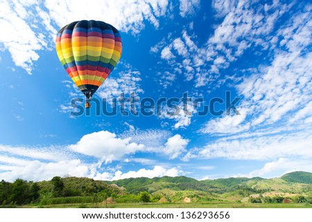 Colorful hot air balloon over green field - stock photo