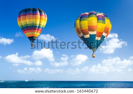 Colorful hot air balloon over the ocean with blue sky background