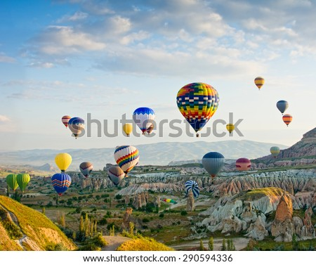 Colorful hot air balloons flying over Red valley at Cappadocia, Anatolia, Turkey. Volcanic mountains in Goreme national park. - stock photo
