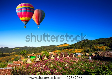 Colorful hot-air balloons flying over the mountain and hot-air balloons flying over mexican sun flower field - stock photo