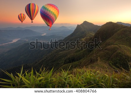 Colorful hot-air balloons flying over the mountain and traveler - stock photo