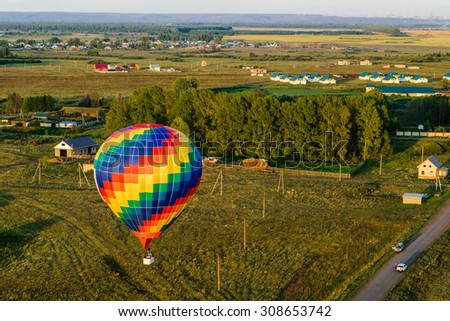 Colorful hot air balloons flying over the village, forest and fields - stock photo
