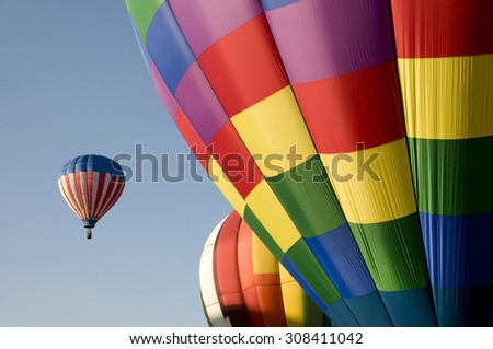 Colorful hot air balloons launching against a blue sky - stock photo