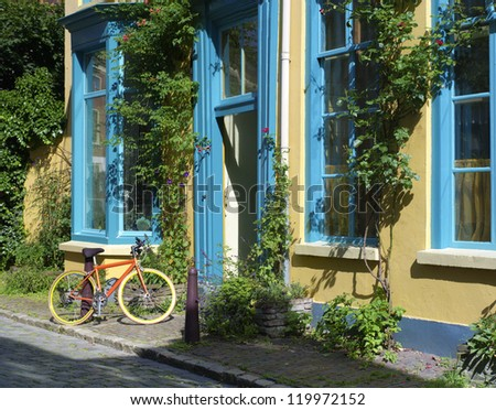 colorful house with a bicycle in front - stock photo