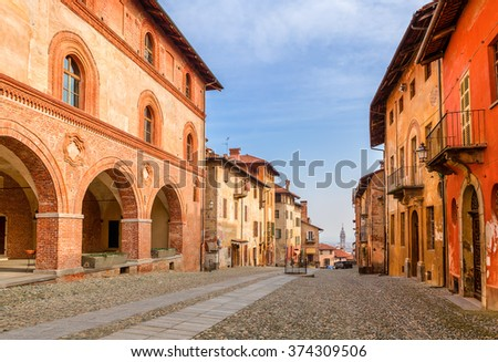 Colorful houses and cobbled street in old town of Saluzzo in Piedmont, Northern Italy. - stock photo