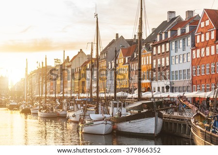 Colorful houses in Copenhagen old town at sunset, with boats and ships in the canal in front of them. - stock photo