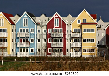 Colorful houses (swedish style) in red, blue and yellow with dark sky - stock photo